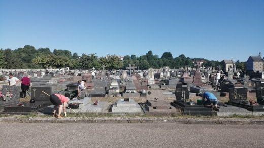 Les bénévoles en train d'enlever les mauvaises herbes autour des tombes.