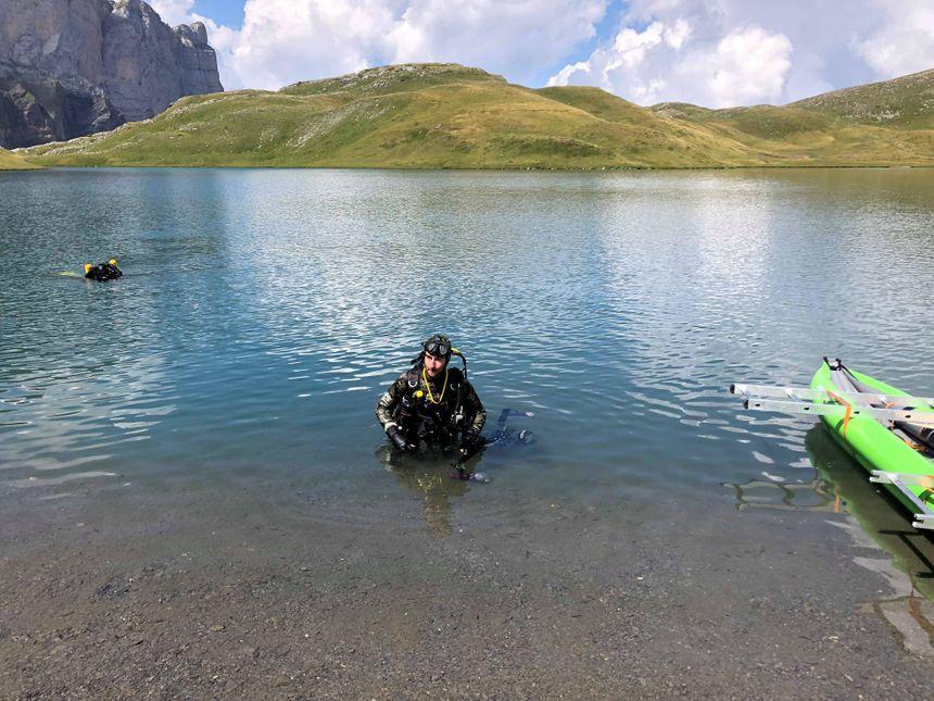 Deux plongeurs récupèrent des sédiments au fond du lac.