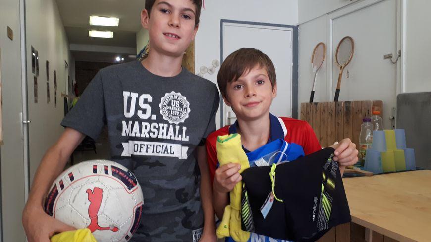 Elouen 11 ans et son petit frère Melvin âgé de 9 ans à la caisse de la recyclerie, les bras chargés de leurs achats.