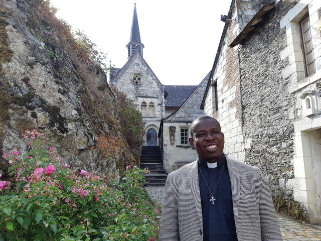 Le père Wakanga devant l'église Notre-Dame de Béhuard