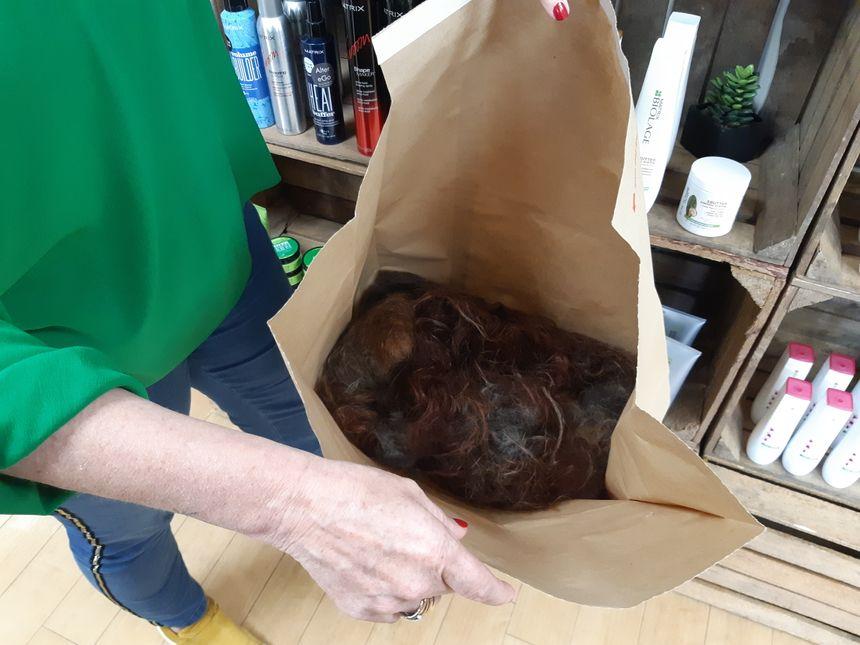 La coiffeuse remplit des sacs de deux kilos chacun.