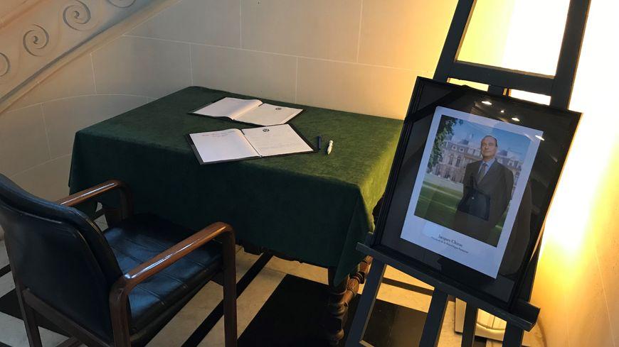 Un livre d'or et un portrait de l'ancien président sont disposés dans le hall de l'hôtel de ville.