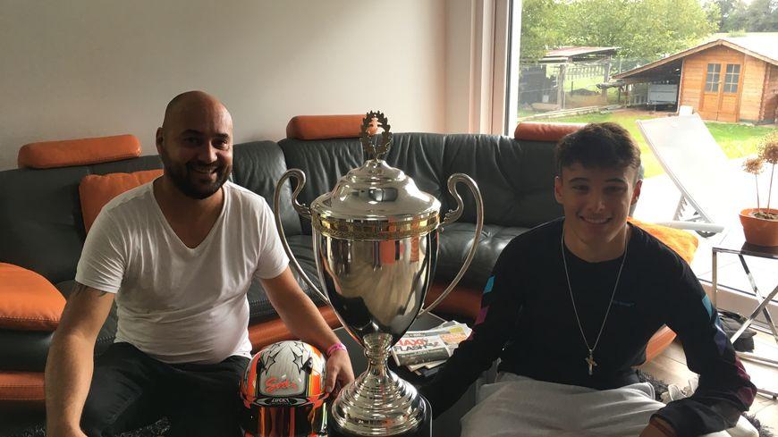 Émilien Denner et son père Eric devant le trophée de champion du monde de karting
