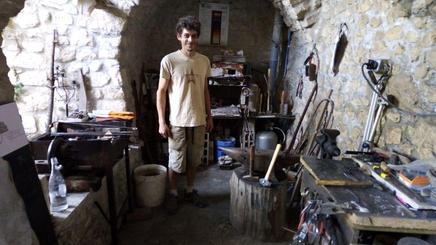 """Le coutelier dans sa """"grotte"""" avec sa forge""""faite maison""""."""