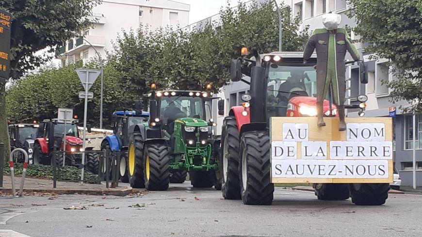"""""""Au nom de la terre, sauvez-nous"""", sur un tracteur dans le centre-ville de La Roche-sur-Yon ce mardi."""