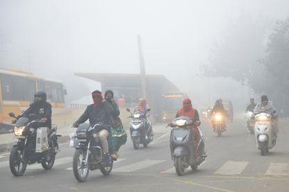 Des Indiens partent travailler le matin en plein smog, un nuage de pollution à Amritsar (13/02/2019)