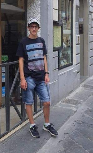 Enzo mesure 1 m 70 et porte un survêtement noir avec un tee shirt gris.