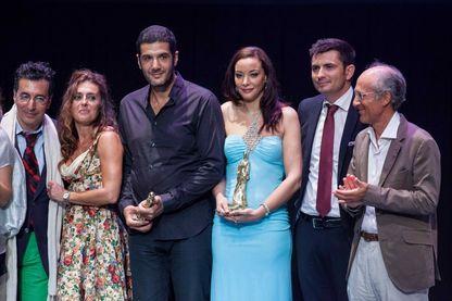 """Le réalisateur franco-marocain Nabil Ayouch (à gauche) et l'actrice marocaine Loubna Abidar (à droite) posent avec leurs trophées pour son film """"Much Loved"""" lors du 8e Festival du Film Francophone d'Angoulême le 30 août 2015."""