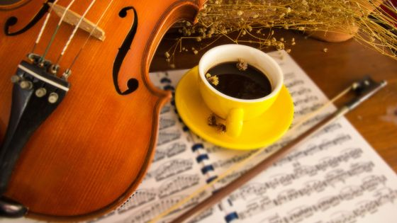High Angle View Of Coffee And Violin With Musical Note On Table