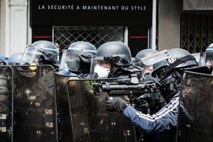 Un policier s'apprête a faire usage de son lbd qui est muni d une camera. Manifestation du 1er Mai 2019 à Paris.