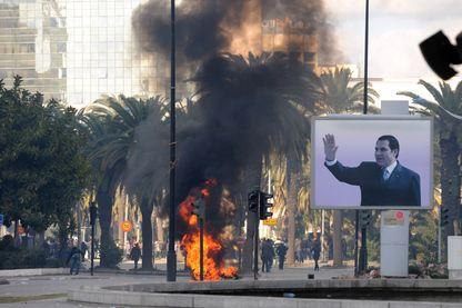 Le 14 janvier 2011, le portrait de Ben Ali trône encore dans les rues de Tunis agitées par les révoltes, mais le dictateur est déjà parti en exil après 23 ans au pouvoir. (photo d'archives)