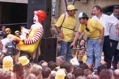 José Bové (2eD), membre fondateur de la Confédération paysanne, regarde la foule porter la statue du clown McDonald, le 1er juillet 2000 sur la place principale de Millau.