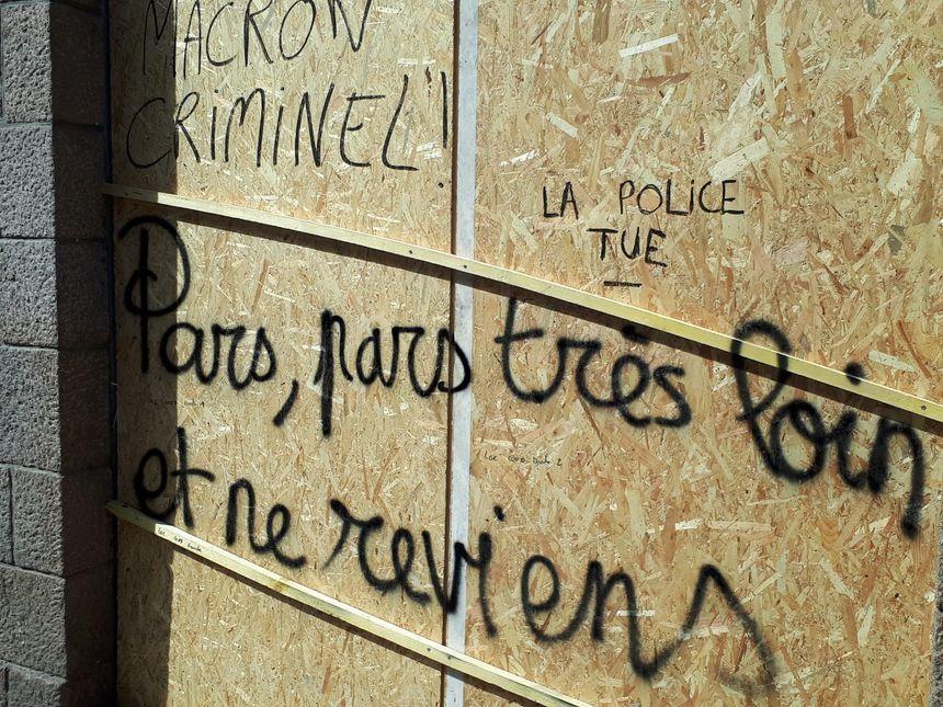 Plusieurs vitrines protégées par des panneaux en bois sont taguées par des manifestants.