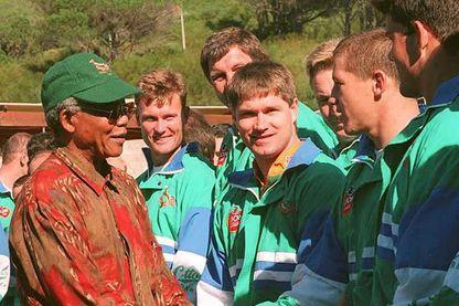 Le président sud-africain Nelson Mandela (à gauche) serre la main de Tiaan Straus, membre de l'équipe nationale sud-africaine de rugby, le 24 mai 1995 au Cap, en présence de ses coéquipiers.