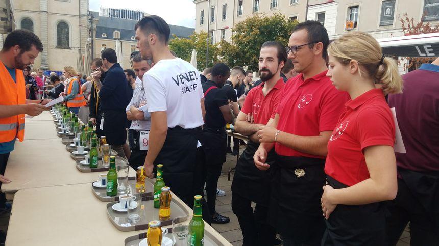 Avant de prendre le départ, les participants s'installent devant leur plateau. Ensuite, ils décapsulent la Tourtel, la verse dans le verre, et ouvre la bouteille de jus de pomme.