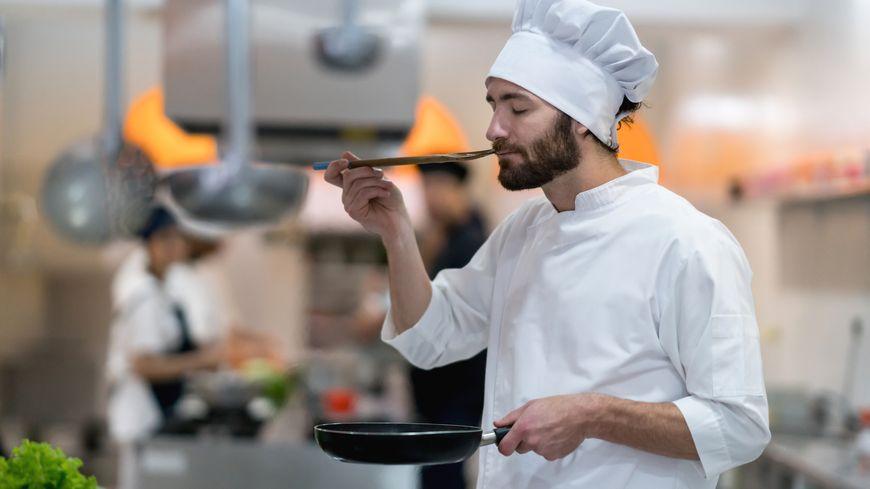 Le chef d'un restaurant gastronomique déguste une sauce qu'il vient de préparer.