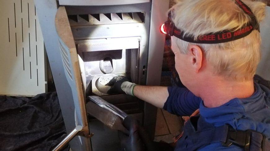 Stéphane Poulmarc'h inspecte l'intérieur du poêle à granulés