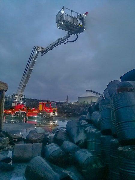 Photo prise par un pompier après l'incendie. Des futs déformés au premier plan, et le silo dans le fond.