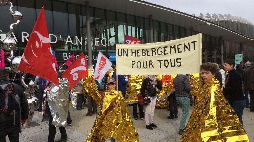"""Couvertures de survie et pancartes à la manifestation """"Un Toit Pour Tous"""" devant la gare d'Annecy, Haute-Savoie"""