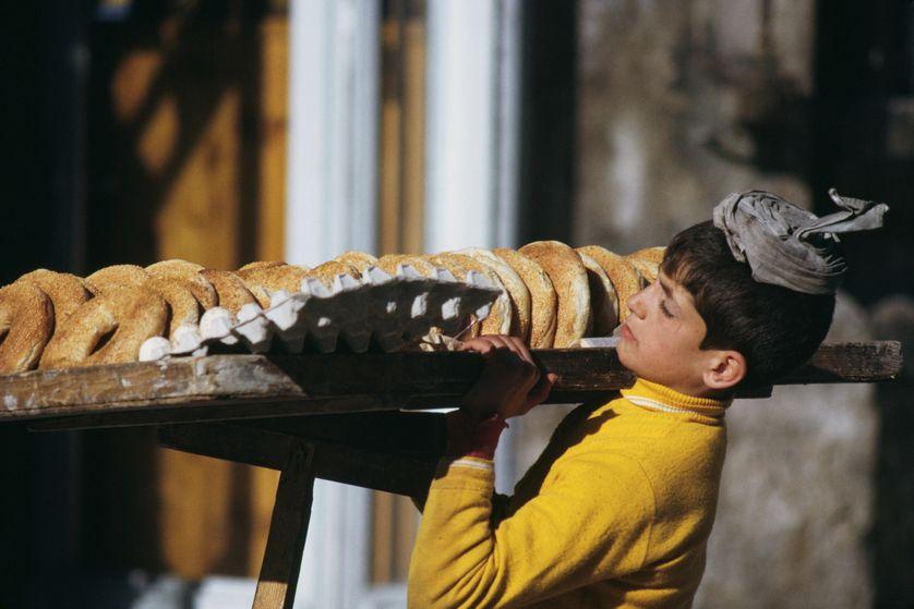 Un garçon portant un plateau de bagels et d'œufs dans la vieille ville de Jérusalem, vers 1970.