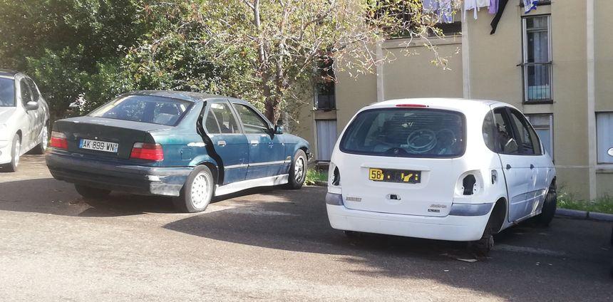Une épave et une voiture ventouse, abandonées sur le parking d'un immeuble à Montesoro