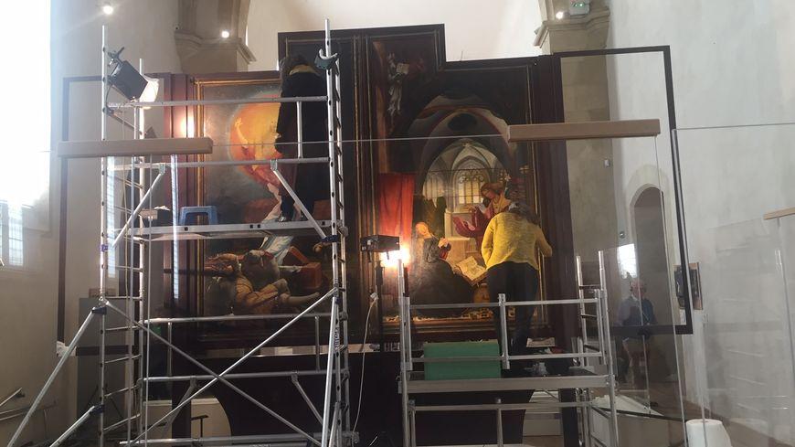 Les restaurateurs en plein travail sur les panneaux peints du retable