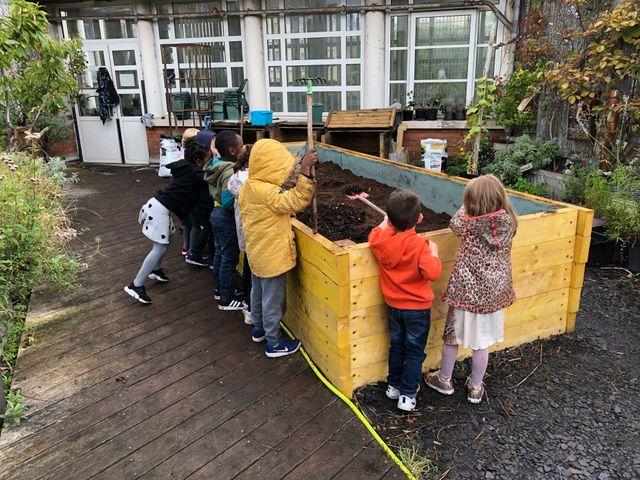 Les élèves réunis autour du bac de permaculture sur le toit de l'école maternelle
