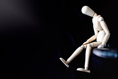 Mannequin en bois solitaire assis seul