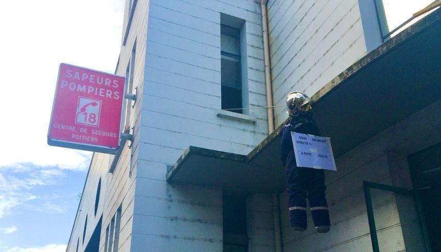 """Un mannequin en tenue de feu suspendu à la caserne de Pont-Achard à Poitiers avec écrit dessus : """"Sous-effectif : on meurt à petit feu"""""""