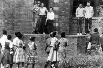 Des élèves blancs et un soldat de la 101e Division aéroportée regardent des élèves noirs se rendre à l'école secondaire Central High School le 27 septembre 1957 à Little Rock, en Arkansas.