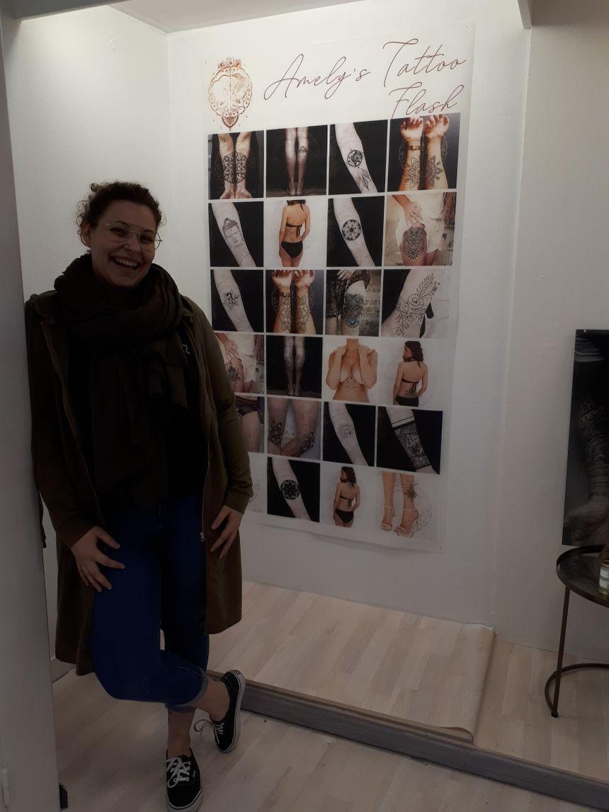La tatoueuse Amélie Gauthier dans son salon à La Flèche, devant les photos de ses créations