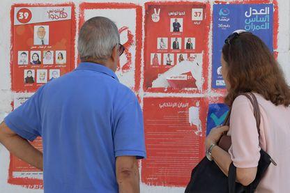 Électeurs tunisiens devant les affiches des partis : jusqu'au dernier moment, de nombreux Tunisiens désenchantés ont hésité pour qui voter, ou à voter tout court.