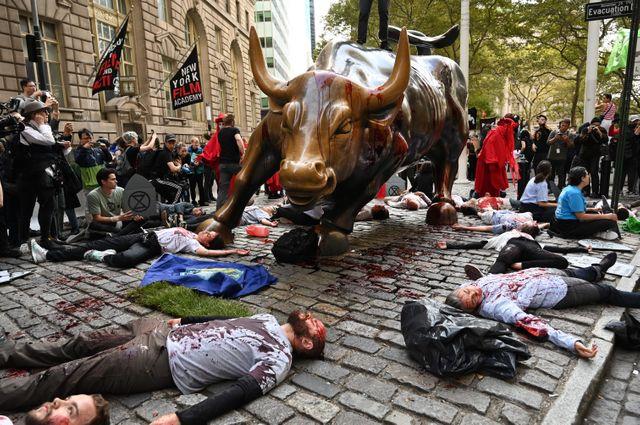 """À New-York, des militants ont aspergé de sang le """"Wall Street Bull"""" et réalisé un """"die-in"""" tout autour."""