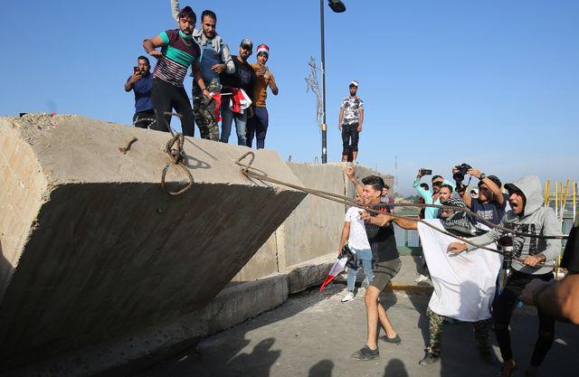 Des manifestants tentent de faire tomber un mur de la Zone Verte de Bagdad qui protège les bâtiments gouvernementaux le 25 octobre