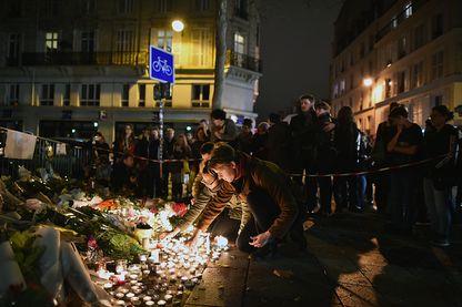 Les gens déposent des fleurs et des bougies sur le trottoir près du lieu de l'attaque terroriste du Bataclan le 14 novembre 2015 à Paris.