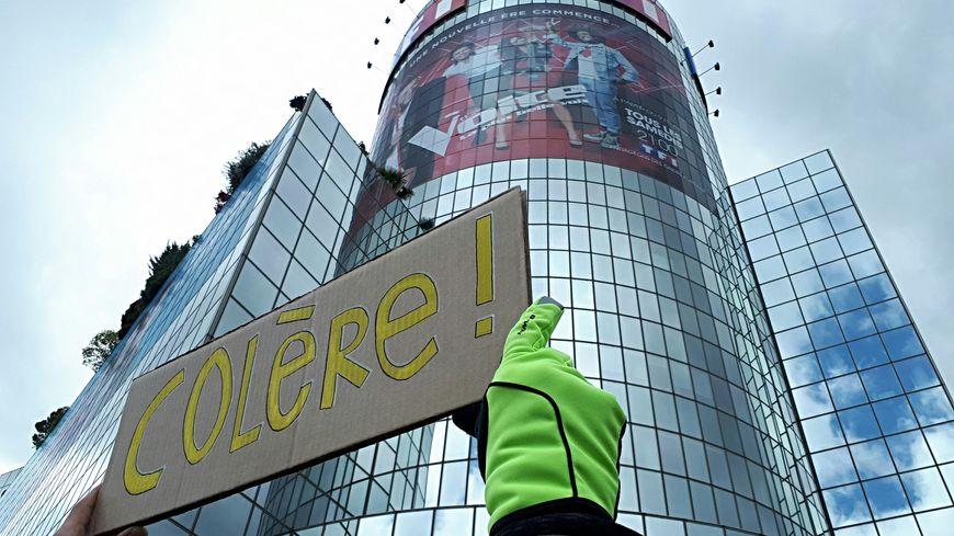"""Le cortège des gilets jaunes fait la """"Tournée des médias"""" et passe devant le siège de TF1 à Boulogne, acte 24, 27 avril 2019. Sur une pancarte : """"Colère""""."""