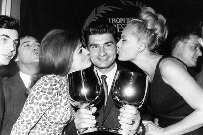 Raymond Poulidor, tenant ses deux coupes, félicité par Dalida et Corinne Marchand, en France le 18 novembre 1964.