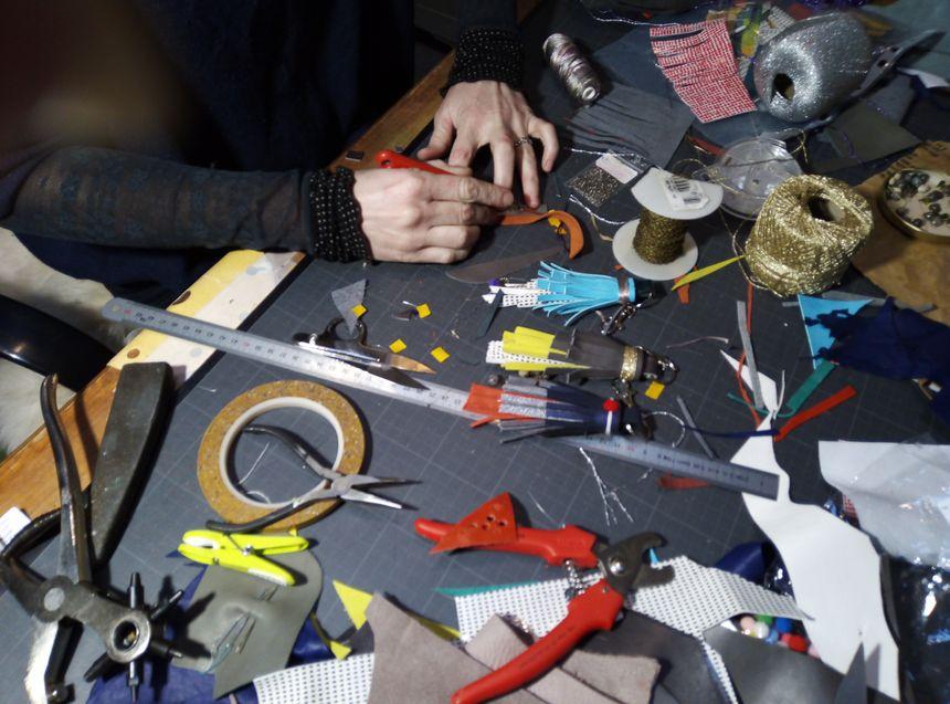 """Les fameux """"pompons"""" d'Agathe, bleu, jaune, rouge, sur sa table de travail."""