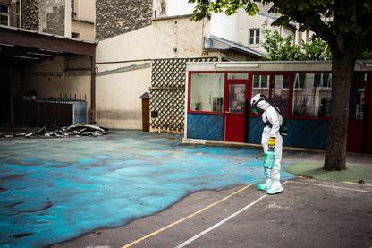 Épandage de gel dans la cour de l'école Saint Benoit, près de Notre-Dame de Paris, durant une opération de décontamination, le 8 août 2019.
