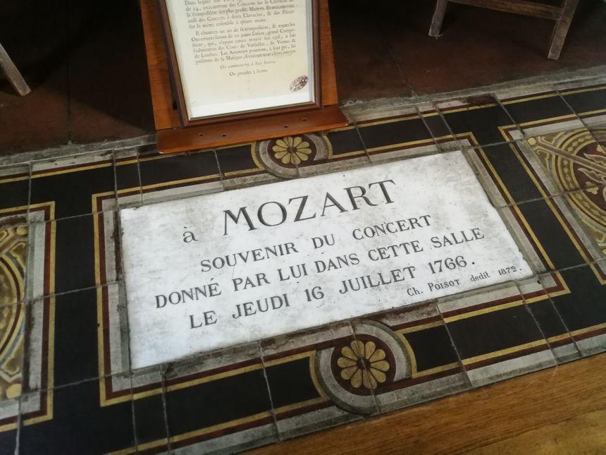 Au pied de cette cheminée, dans la salle de lecture, une plaque rappelle que Mozart est venu jouer à Dijon dans cette pièce