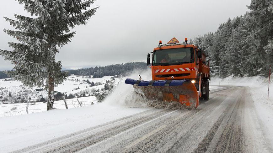 Un chasse-neige sur une route enneigée d'Auvergne-Rhône-Alpes.