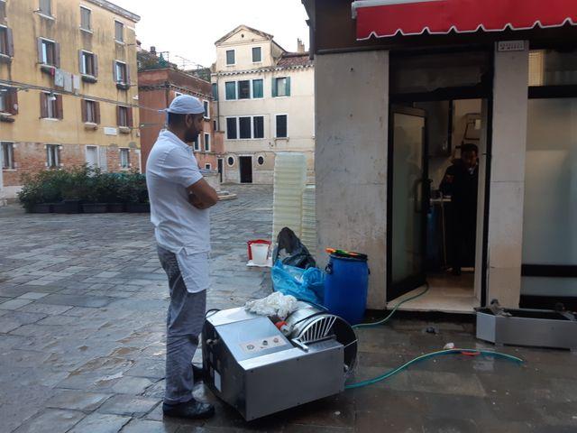 Un restaurateur résigné vide sa cuisine totalement inondée au lendemain de l'acqua alta de 187 cm
