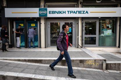 Des personnes faisant la queue pour retirer de l'argent à un guichet automatique devant une succursale de la succursale de la Banque nationale de Grèce à Thessalonique, le 4 octobre 2018.
