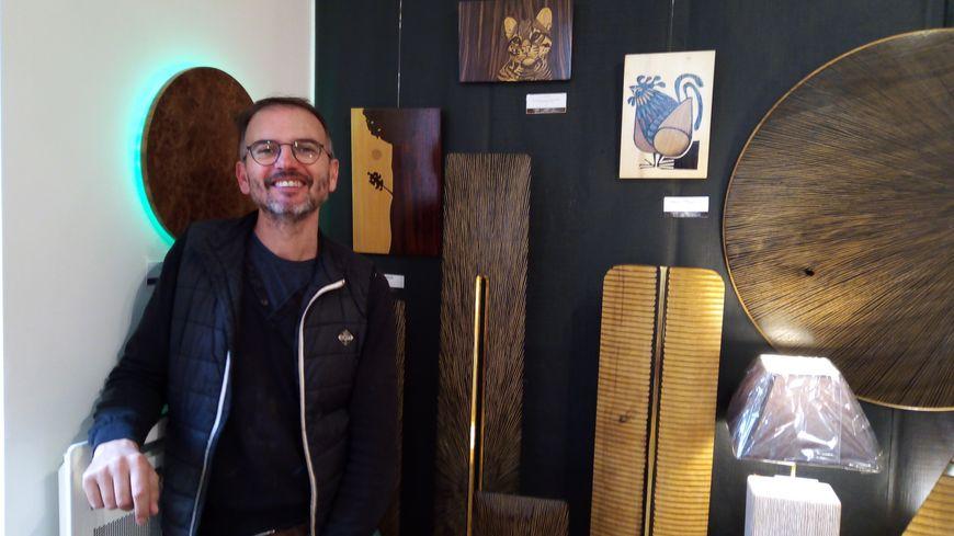 Landry Clément devant quelques unes de ses sculptures dorées à la feuille.