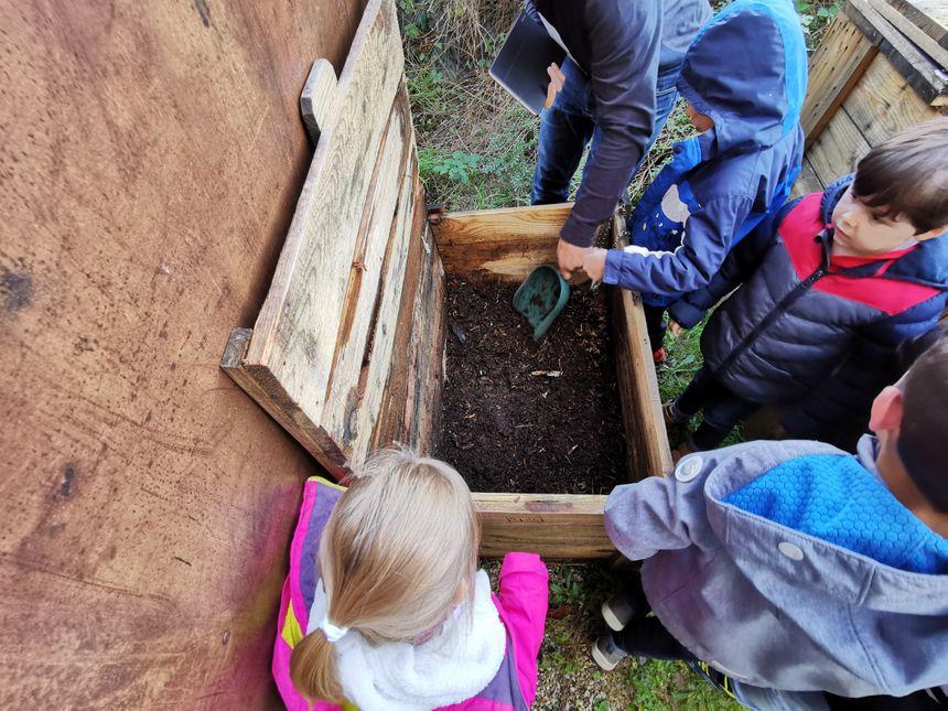 Entre deux seaux de déchets, les enfants sont invités à mettre une petite pelletée de terre ... et ils s'y prennent avec sérieux !