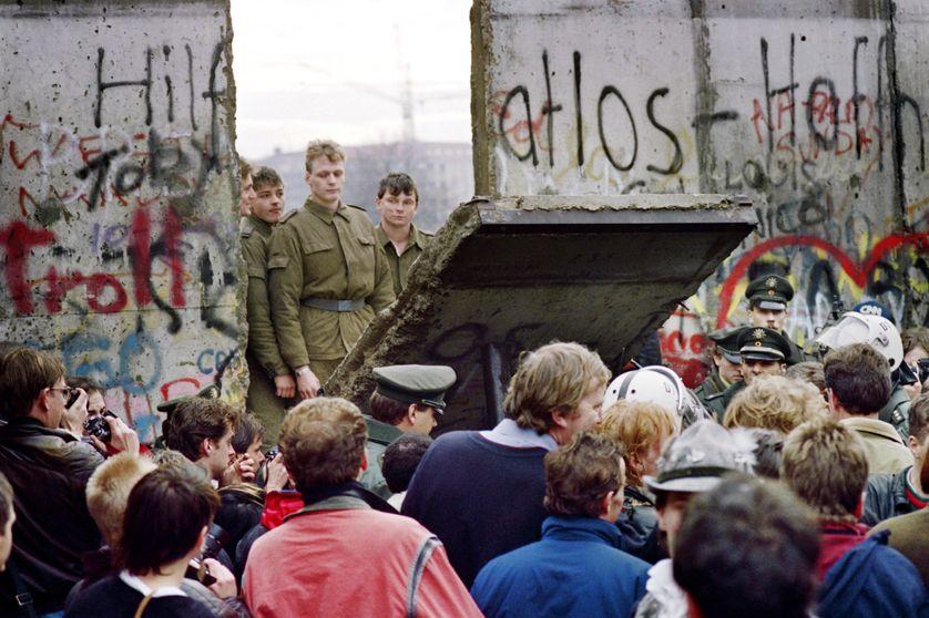 Les Berlinois de l'Ouest se rassemblent devant le mur alors que des soldats de l'Est commencent à le détruire, le 11 novembre 1989, entre Berlin-Est et Berlin-Ouest, près de la place Potsdamer.