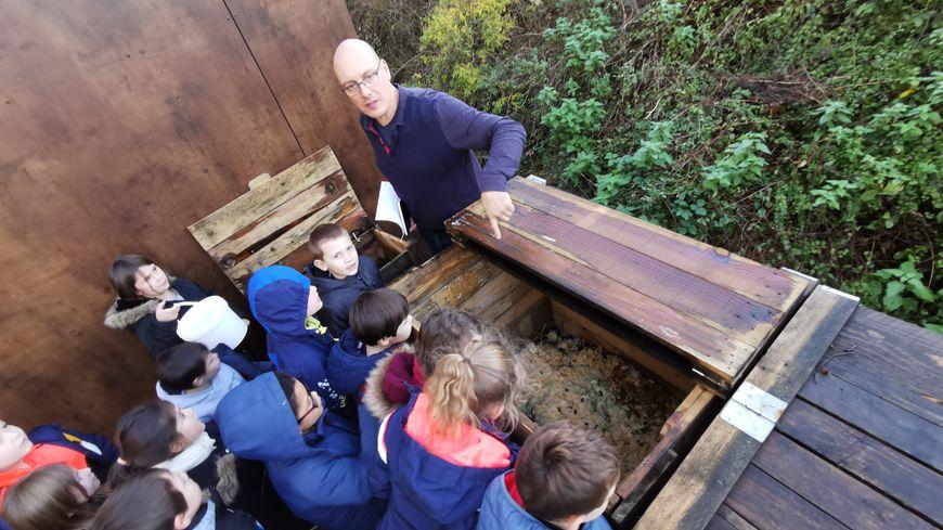 Christophe Charrier, chargé environnement à la ComCom du Pays de Meslay-Grez, fait découvrir le bac de compostage flambant neuf aux enfants de Bouère.