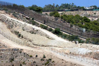 Photo prise le 9 juillet 2014 dans la ville côtière de Nador, au Maroc. Au premier plan, une tranchée creusée face à une clôture (en arrière-plan) séparant le Maroc de l'enclave espagnole de la ville de Melilla