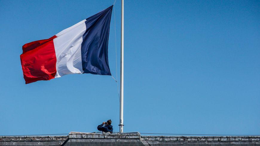 Le drapeau tricolore en berne sur les Invalides à Paris