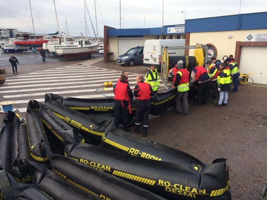 Les pompiers et du personnel du port déploient les bouées qui serviront de rempart face à une pollution par exemple aux hydrocarbures
